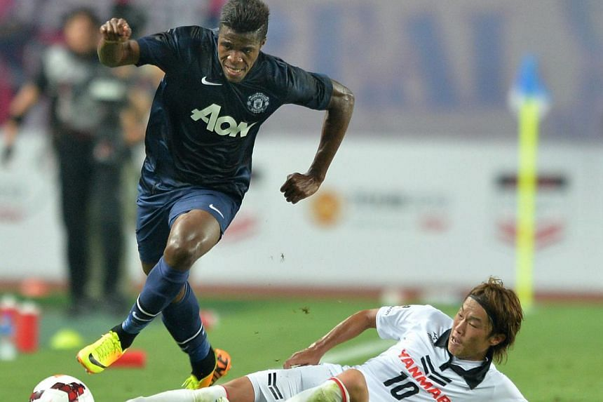 Manchester United midfielder Wilfried Zaha (left) clears a sliding tackle by Cerezo Osaka midfielder Jumpei Kusukami during their friendly football match at Nagai Stadium in Osaka on July 26, 2013. Zaha scored his first ever goal for the English cham