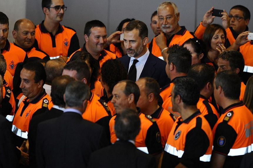 Spain's Crown Prince Felipe (centre) greets first responders who took part in the rescue operations following the July 24 train crash in Santiago de Compostela, north-western Spain, on July 26, 2013. After the deadly high-speed train crash that struc