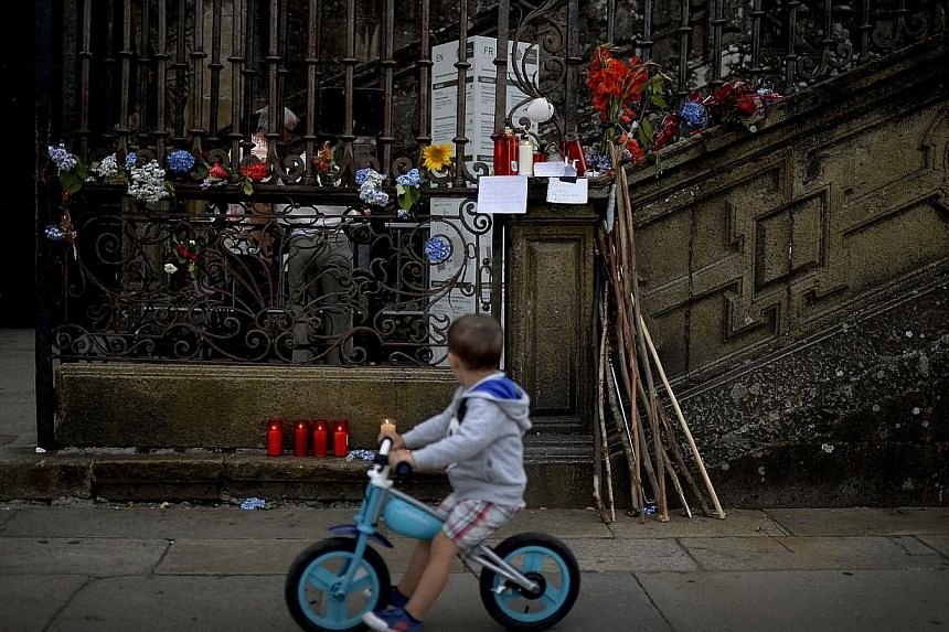 A child cycles past flowers placed in memory of the victims of Wednesday's train crash, in front of the cathedral of Santiago de Compostela, north-western Spain, on July 26, 2013. After the deadly high-speed train crash that struck on the rails below