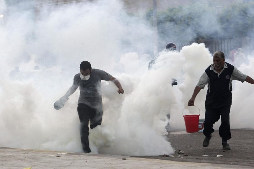 Supporters of deposed Egyptian president Mohamed Mursi run from tear gas fired at them by police during clashes in Nasr city area, east of Cairo on Saturday, July 27, 2013. Egyptian police shot dead 23 supporters of Mr Mursi and wounded hundreds more