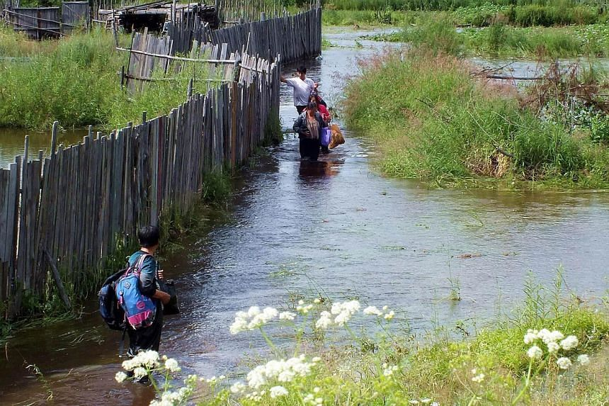 Local residents wade in a flooded area in Yakeshi, in northern China's Inner Mongolia region on Thursday, July 25, 2013. -- PHOTO: AFP