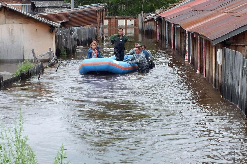 Local residents travel in a rubber dingny in a flooded area in Yakeshi, in northern China's Inner Mongolia region, on Thursday, July 25, 2013. -- PHOTO: AFP