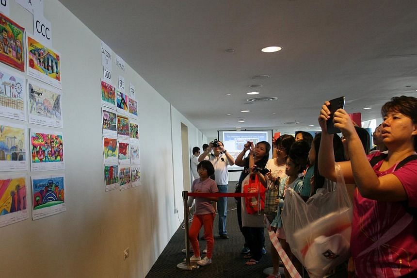 Excited participants and their families check the walls to see if their artworks had been chosen as finalists of the Little Red Dot-Beautex Life's Beautiful Art Competition on Saturday, July 27, 2013. -- ST PHOTO: SERENE LUO