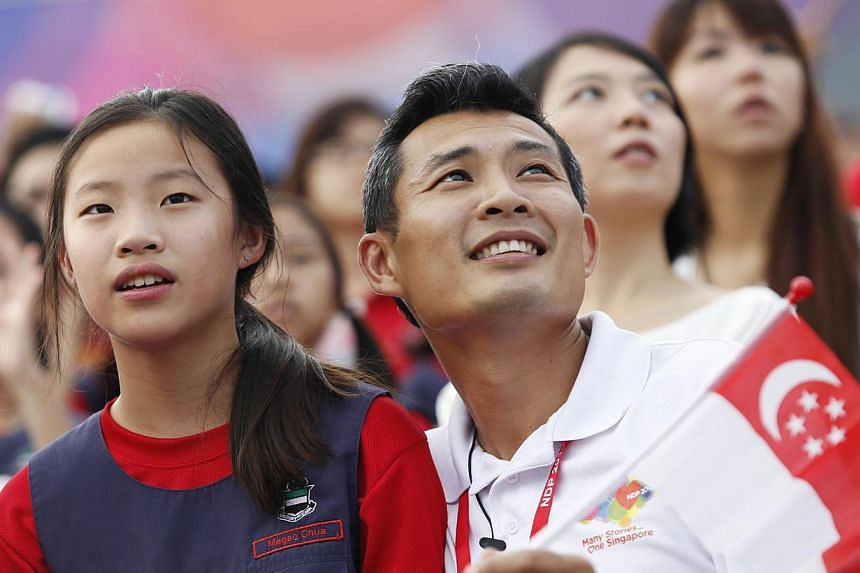 Colonel Chua and his daughter, Megan Chua, 11, at the National Day Parade, National Education Show 3 on July 27, 2013. -- ST PHOTO: DESMOND LUI