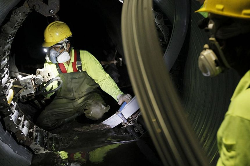 Workers using the spiral wound lining method, that relies on interlocking PVC strips, to repair a sewer on Thursday.