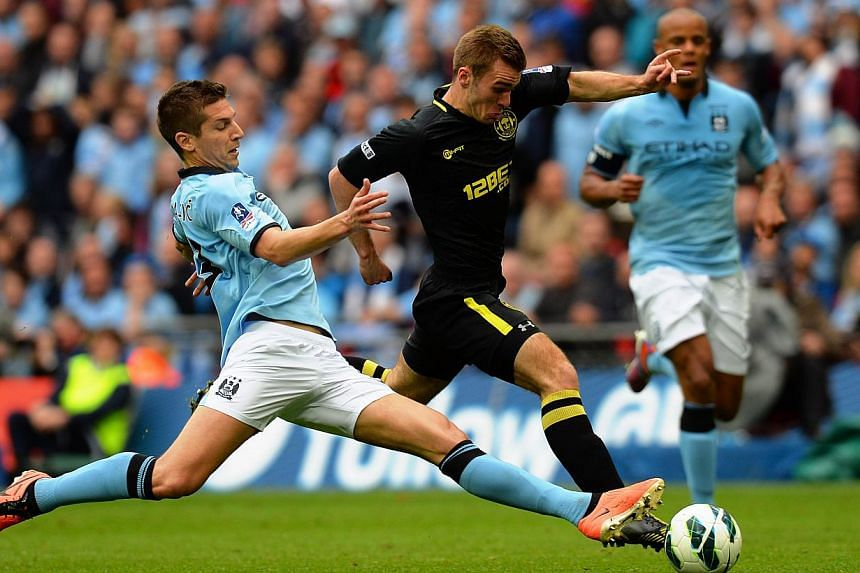 Wigan Athletic's English striker Callum McManaman (R) dribbles the ball through the stretching challenge of Manchester City's Serbian defender Matija Nastasic (L) during the English FA Cup final football match between Manchester City and Wigan Athlet