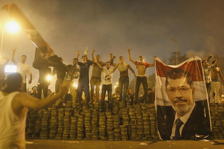 Supporters of deposed Egyptian President Mohamed Mursi hold a Mursi poster as they stand on a barricade built to separate them from police during clashes in Nasr city area, east of Cairo, July 27, 2013.At least 65 people were killed during clas