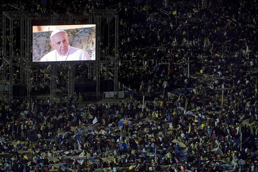 A live image of Pope Francis is broadcast at a vigil with pilgrims on Copacabana beach in Rio de Janeiro, Brazil, Saturday, July 27, 2013. -- PHOTO: AP