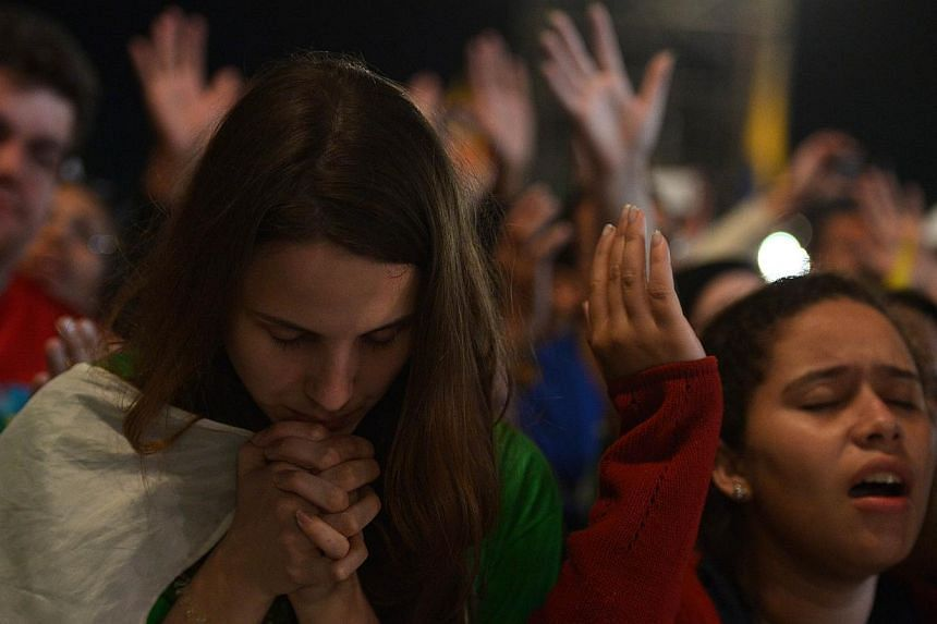 Catholic pilgrims attending World Youth Day (WYD) take part in a prayer vigil headed by Pope Francis, at Copacabana beach in Rio de Janeiro on July 27, 2013. -- PHOTO: AFP