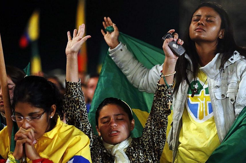"""Pilgrims pray as Pope Francis celebrates mass at Copacabana Beach on his sixth day in Rio de Janeiro, July 27, 2013. Pope Francis urged young Catholics in Brazil to become """"athletes of Christ"""" on Saturday, telling them Jesus offers something """"bigger"""