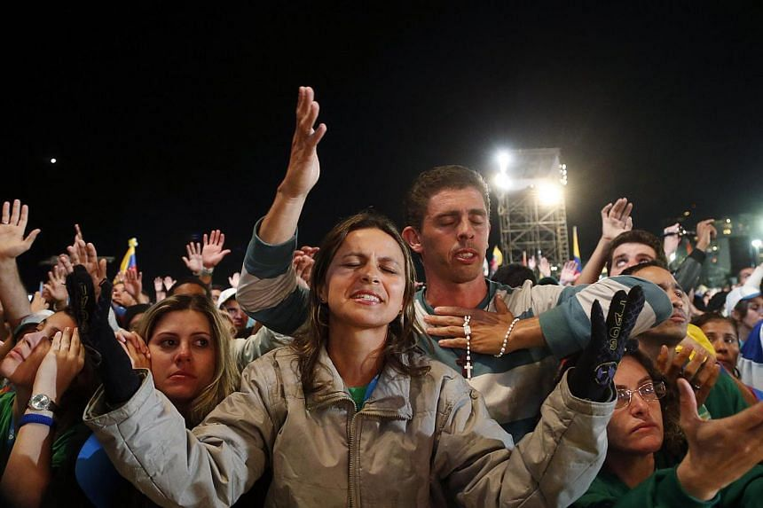 Pilgrims pray as Pope Francis celebrates mass at Copacabana Beach on his sixth day in Rio de Janeiro, July 27, 2013. -- PHOTO: REUTERS