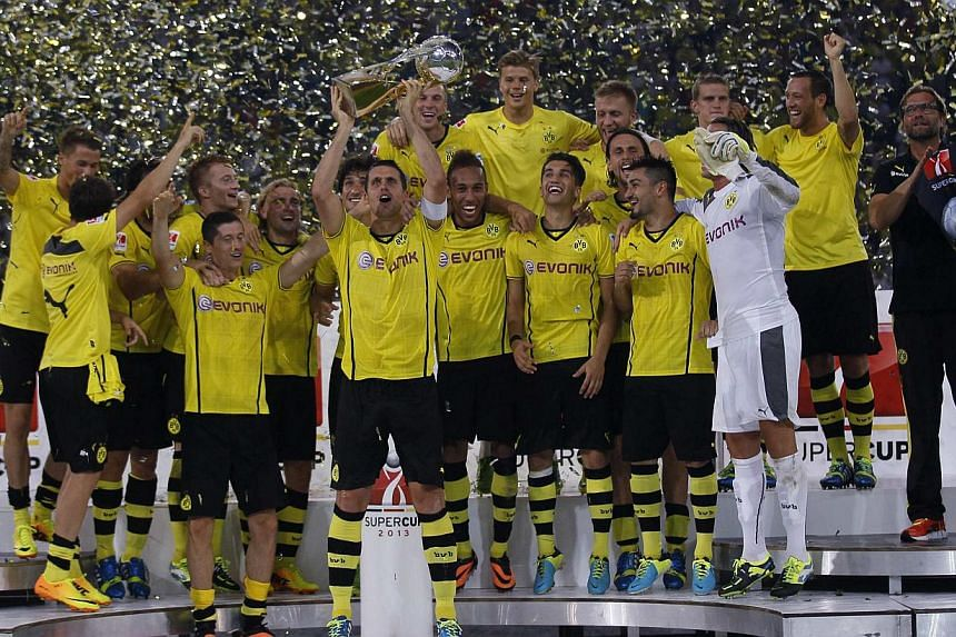 Borussia Dortmund's Sebastian Kehl lifts the German SuperCup trophy after their 4-2 victory over Bayern Munich in their SuperCup 2013 soccer match in Dortmund July 27, 2013. Seen with them is Borussia Dortmund coach Juergen Klopp (R). Borussia Dortmu