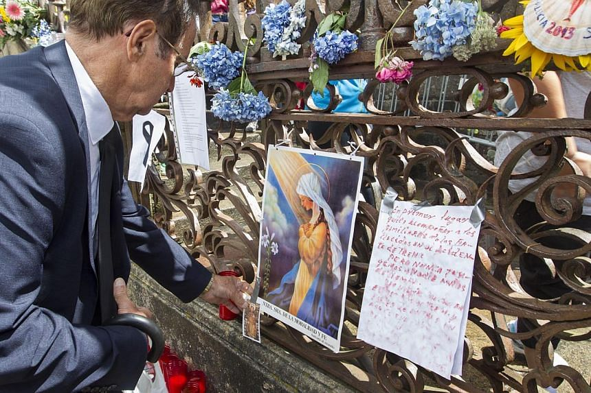 A man places a card on a makeshift candle and flower shrine outside the cathedral for the train crash victims in Santiago de Compostela, Spain, Saturday July 27, 2013. -- PHOTO: AP