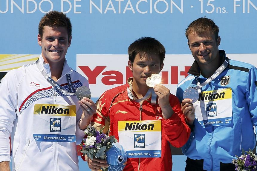 Gold medallist Qiu Bo of China (centre) poses with other medallists at the men's 10m platform victory ceremony during the World Swimming Championships at the Montjuic municipal pool in Barcelona on Sunday, July 28, 2013. Qiu made amends for the disap