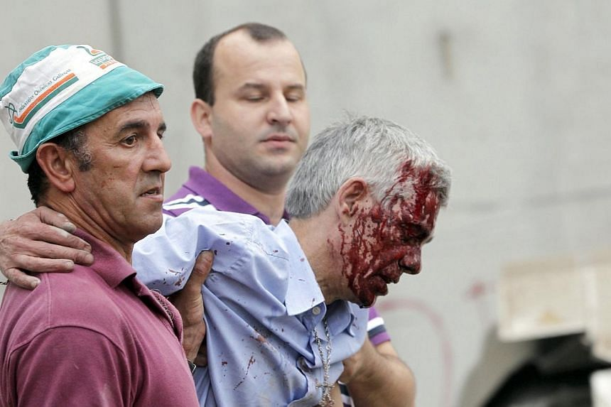 Train driver Francisco Jose Garzon (right) is helped by two men after his train crashed near Santiago de Compostela, northwestern Spain, July 24, 2013. -- FILE PHOTO: REUTERS