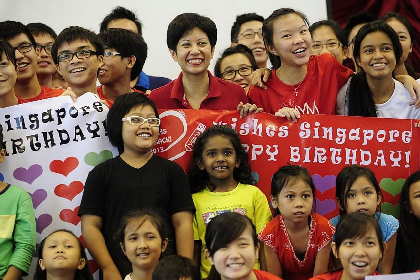 """Tanjong Pagar GRC MP Indranee Rajah (centre) poses for photos with children from Thye Hua Kwan Family Service Centreand volunteers from Anderson Junior College at the start of the """"Youths Give Back! 2013"""" project on Sunday, July 28, 2013. -- ST"""