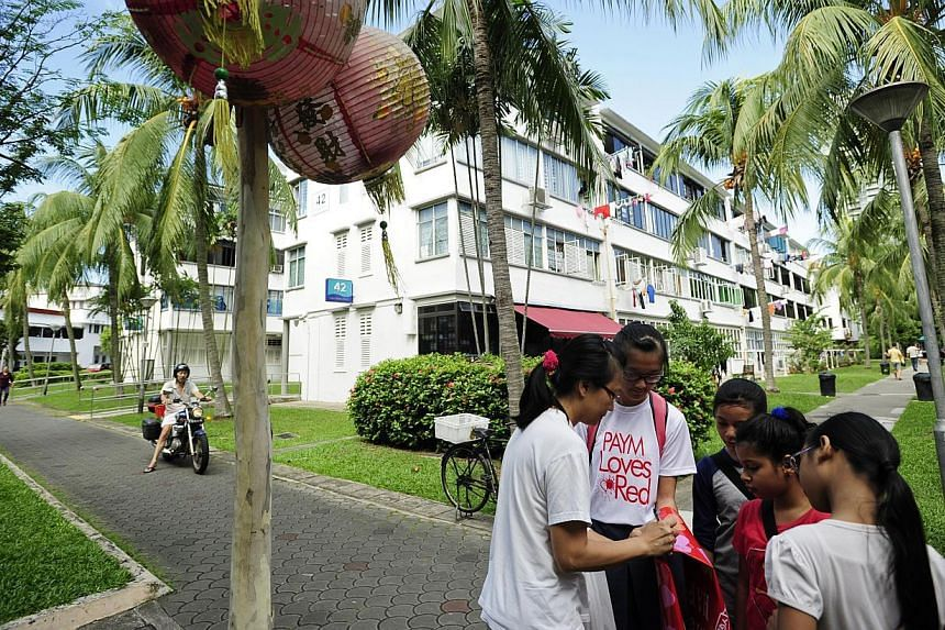 Student volunteer Charmaine Goh (second from left) and children fromThye Hua Kwan Family Service Centreget 45-year-old Tiong Bahru resident Janet Chia (left) to write her birthday wishes for Singapore on a banneron Sunday, July 28,&