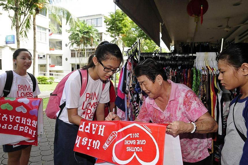 Student volunteer Charmaine Goh (left) and11-year-old Nur Syazlin Mahadi from Thye Hua Kwan Family Service Centreget 73-year-old Madam Zhu Ming Ying, who owns a shop at Tiong Bahru Market, to write her birthday wishes for Singapore on a b