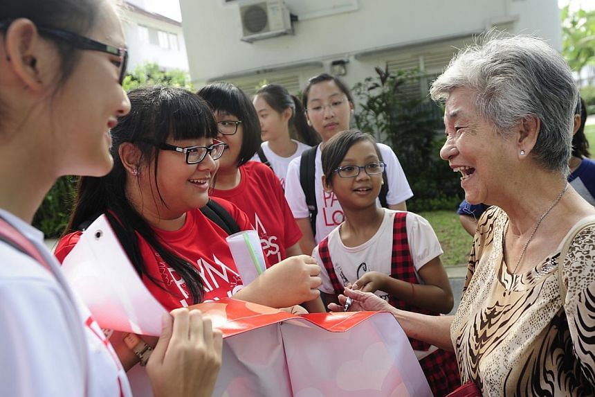 (From left) Student volunteersCharmaine Goh and Jaslynn Oei and 11-year-old Nur Hazelynna Abdullah from Thye Hua Kwan Family Service Centretalk to 85-year-old Tiong Bahru resident Xiao Yue He and get her to write her birthday wishes for S