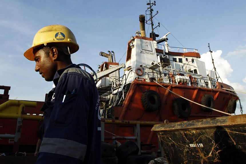 A worker walks past a Swiber support vessel at one of their shipyards in Singapore July 10, 2013.Offshore oil and gas construction and services provider Swiber Group has won new contracts worth US$435 million (S$549.9 million). -- PHOTO: REUTER