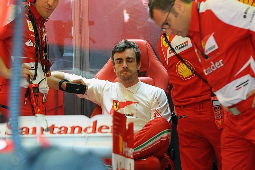 Ferrari's Spanish driver Fernando Alonso sits in the pits during the first practice session at the Hungaroring circuit in Budapest on July 26, 2013 ahead of the Hungarian Formula One Grand Prix. Fernando Alonso on Sunday tried to distance himself fro
