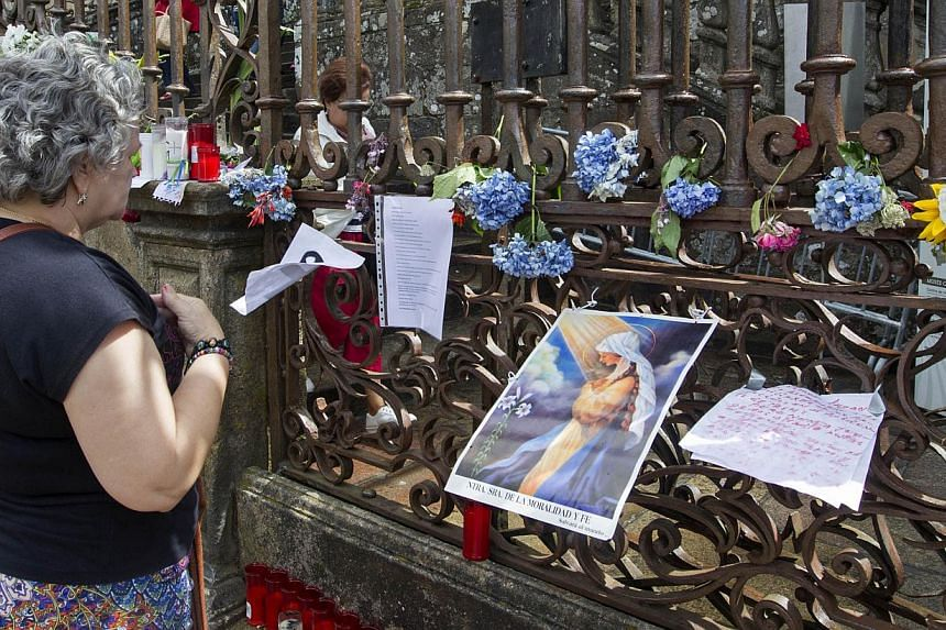 A woman prays in front of a makeshift candle and flower shrine outside the cathedral for the train crash victims in Santiago de Compostela, Spain, Saturday July 27, 2013. -- PHOTO: AP
