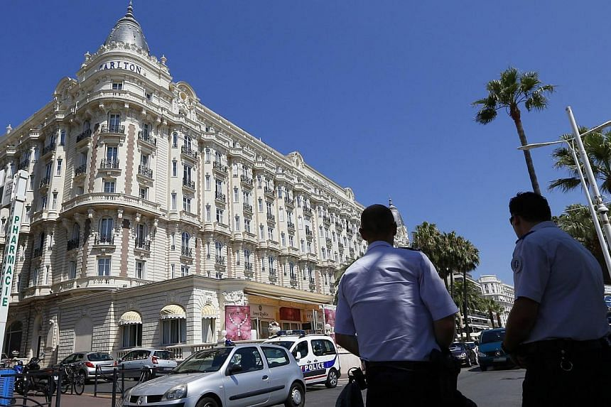 """French policemen keep watch outside the Carlton Hotel on July 28, 2013 in the French Riviera resort of Cannes, after an armed man held up the jewellery exhibition """"Extraordinary diamonds"""" of the Leviev diamond house, making away with jewels estimated"""