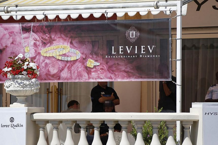 """French policemen investigate outside the Carlton Hotel on July 28, 2013 in the French Riviera resort of Cannes, after an armed man held up the jewellery exhibition """"Extraordinary diamonds"""" of the Leviev diamond house, making away with jewels estimate"""