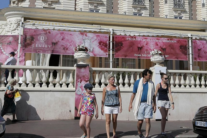 People walk by the Carlton hotel, in Cannes, southern France, the scene of a daylight raid on Sunday, July 28, 2013. -- PHOTO: AP
