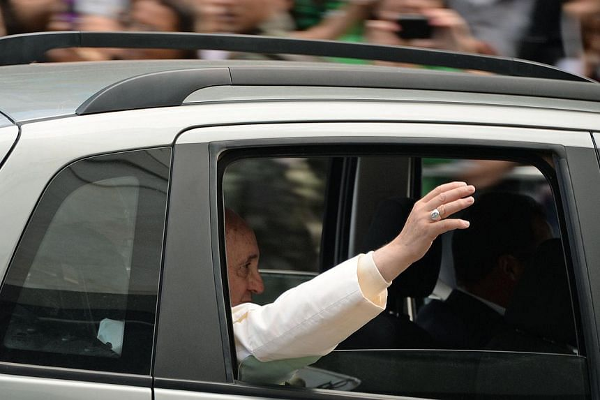 Pope Francis waves as he leaves Copacabana beach in Rio de Janeiro, on July 28, 2013 after celebrating the final mass of his visit to Brazil. -- PHOTO: AFP