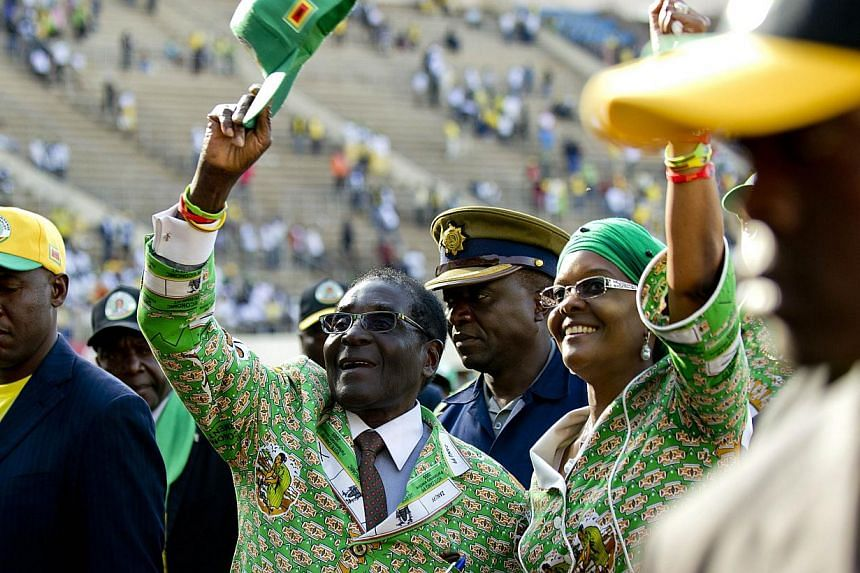 Zimbabwe's President Robert Mugabe (centre) greets his supporters alongside his wife Grace after his address at a rally in Harare on July 28, 2013.President Robert Mugabe on Sunday made his final call for peaceful voting as he vowed that the up