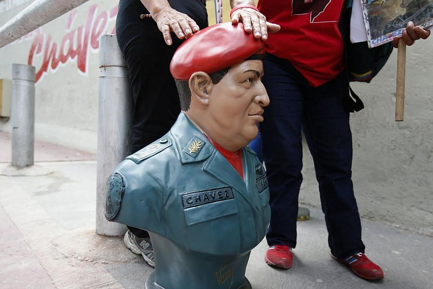 A woman touches a bust of the late Venezuelan President Hugo Chavez, outside his mausoleum in Caracas, on July 28, 2013. Supporters of Chavez gathered in various parts of the country on Sunday to commemorate his 59th birthday, according to local medi