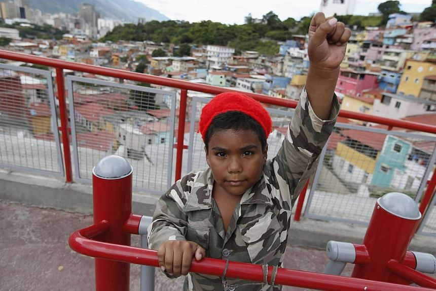 A boy dressed as the late Venezuelan President Hugo Chavez gestures as he poses for a photograph outside Chavez's mausoleum in Caracas, on July 28, 2013. Supporters of Chavez gathered in various parts of country on Sunday to commemorate his 59th birt
