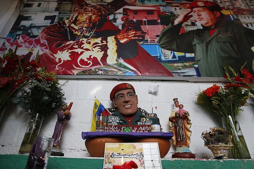 Candles and flowers are displayed inside a chapel dedicated to the late Venezuelan President Hugo Chavez, outside his mausoleum in Caracas, on July 28, 2013. Supporters of Chavez gathered in various parts of the country on Sunday to commemorate his 5