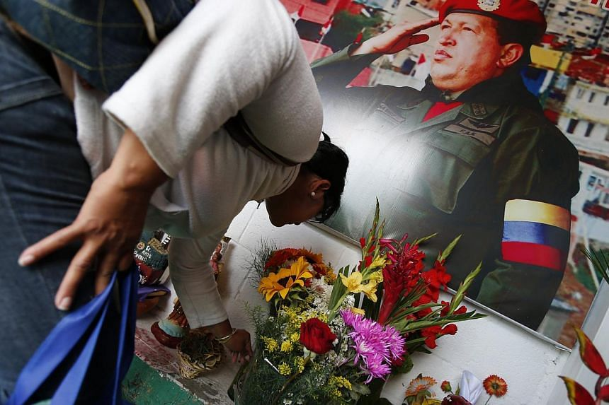 A woman places flowers inside a chapel dedicated to the late Venezuelan President Hugo Chavez, outside his mausoleum in Caracas, on July 28, 2013. Supporters of Chavez gathered in various parts of the country on Sunday to commemorate his 59th birthda