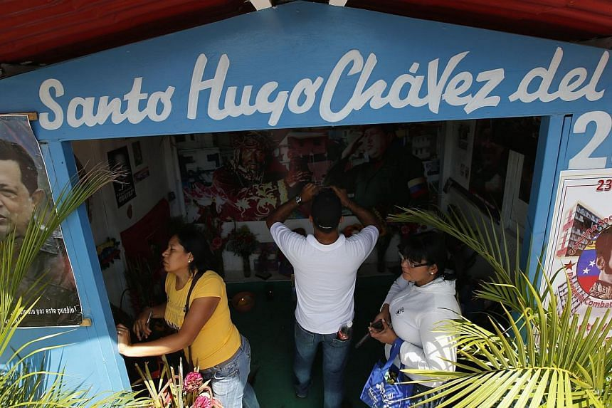 Visitors stand inside a chapel dedicated to the late Venezuelan President Hugo Chavez, outside his mausoleum in Caracas, on July 28, 2013. Supporters of Chavez gathered in various parts of the country on Sunday to commemorate his 59th birthday, accor