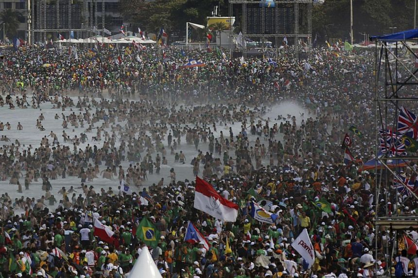 Faithfuls try to get a glimpse of Pope Francis as he leaves Copacabana beach in Rio de Janeiro, on July 28, 2013 after celebrating the final mass of his visit to Brazil. -- PHOTO: AFP