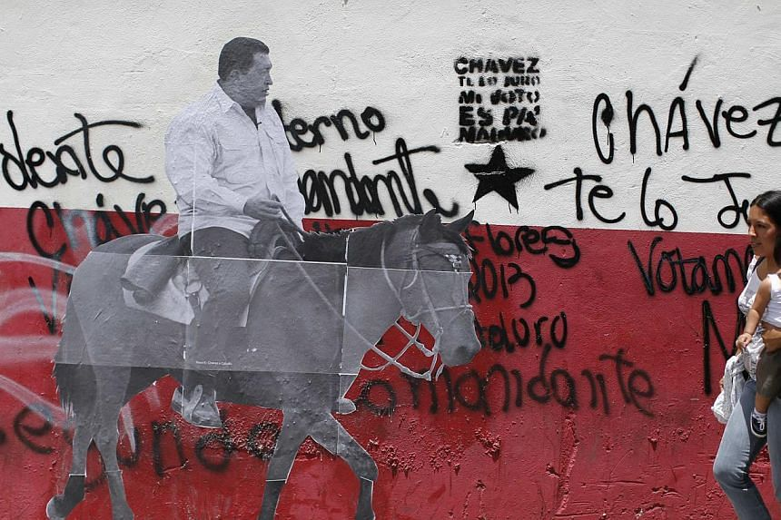 A woman carrying a child passes a picture showing the late Venezuelan President Hugo Chavez riding a horse, in Caracas on July 28, 2013. Supporters of Chavez gathered in various parts of the country on Sunday to commemorate his 59th birthday, accordi