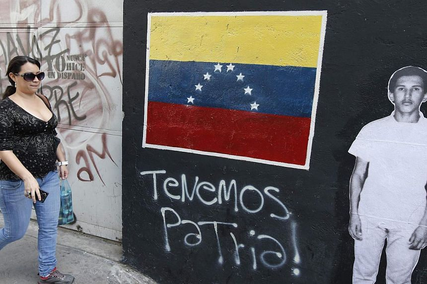 A woman walks past a picture of the late Venezuelan President Hugo Chavez next to a painting of a Venezuelan flag, in Caracas on July 28, 2013. Supporters of Chavez gathered in various parts of the country on Sunday to commemorate his 59th birthday,