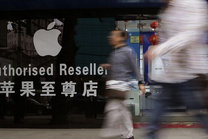 People walk past outside a mobile phone store selling Apple products in Wuhan, Hubei province on April 18, 2013. Three Chinese factories making Apple products impose excessive overtime and employ minors, a US-based advocacy group said on Monday, July