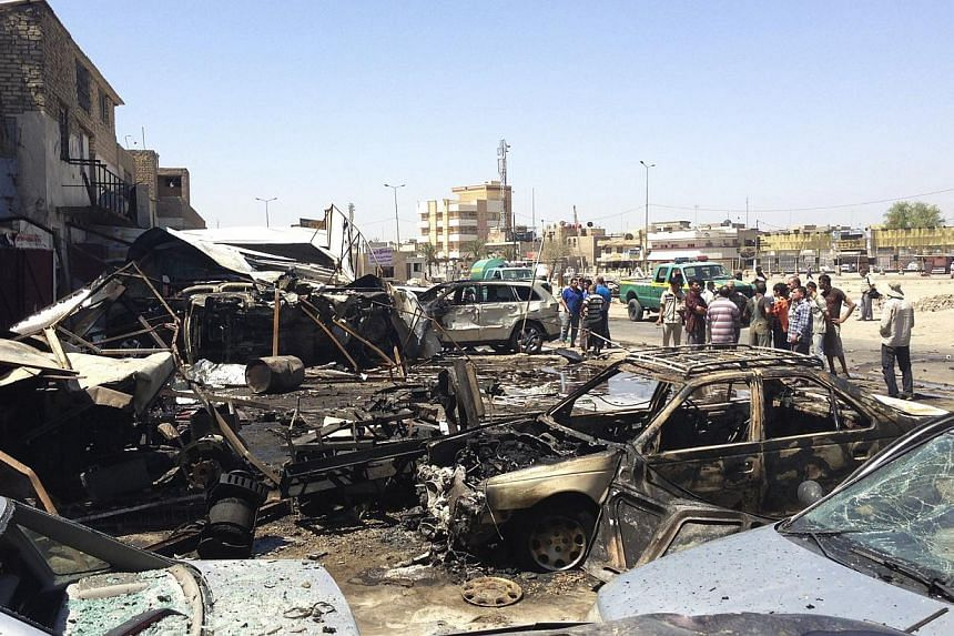 Residents gather at the site of a car bomb attack in the Hurriya District in Baghdad on Monday, July 29, 2013. A wave of car bombs struck in and around Baghdad on Monday morning, killing at least 29 people, security and medical officials said. -- PHO