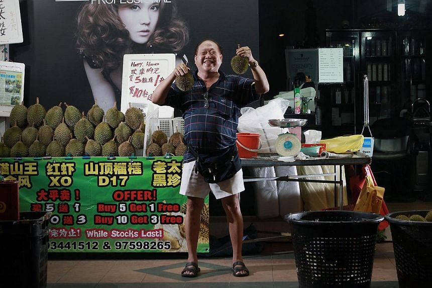 Durian seller Yap Kean Seng (above), is known for giving away free durians during his birthday every year. -- ST PHOTO: NEO XIAOBIN