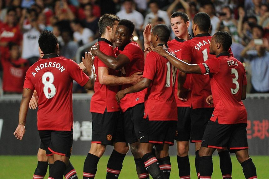 Manchester United players celebrate a goal against Kitchee during their football friendly match at Hong Kong stadium on Monday, July 29, 2013. Manchester United beat Kitchee 5-2 in a football friendly on Monday in Hong Kong. -- PHOTO: AFP