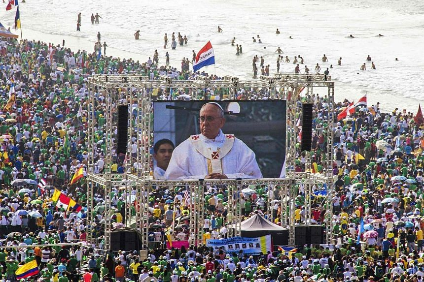 Pilgrims watch Pope Francis on a video screen as he celebrates mass on Copacabana Beach in Rio de Janeiro, July 28, 2013. -- PHOTO: REUTERS