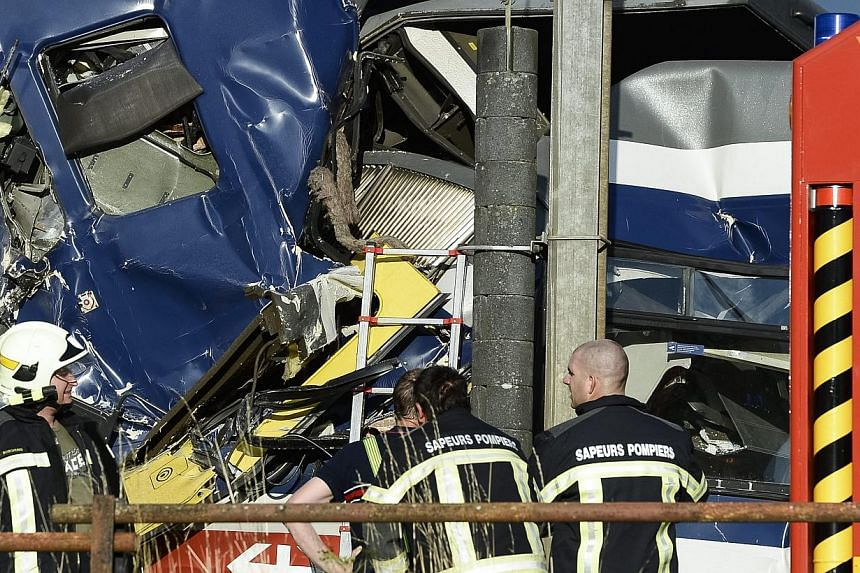 Rescue personnel work at the site where two passenger trains collided head-on in Granges-pres-Marnand, western Switzerland, on Monday, July 29, 2013. Numerous people have been injured. -- PHOTO: AP