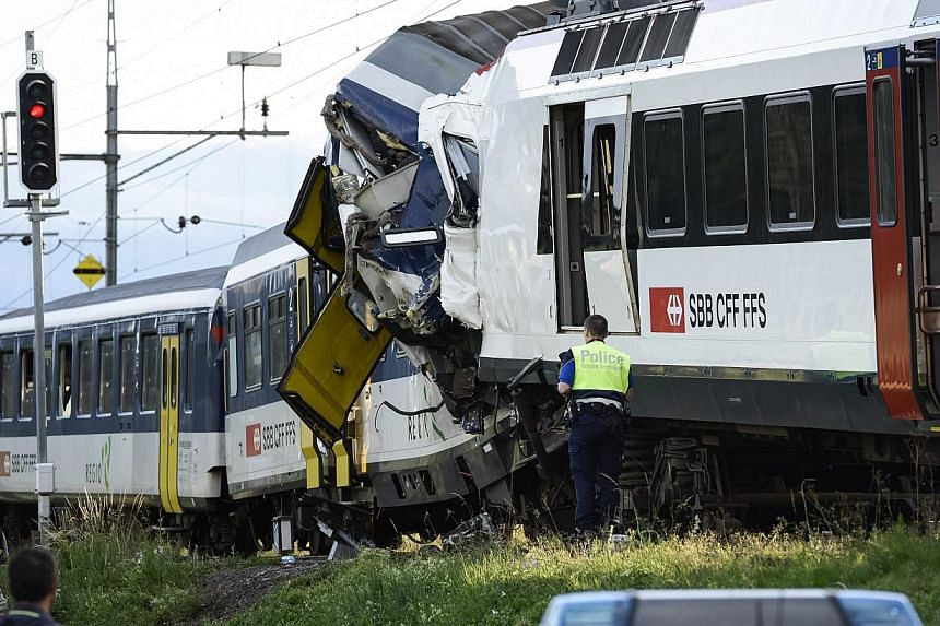 Police inspect the site where two passenger trains collided head-on in Granges-pres-Marnand, western Switzerland, on Monday, July 29, 2013. Numerous people have been injured. -- PHOTO: AP