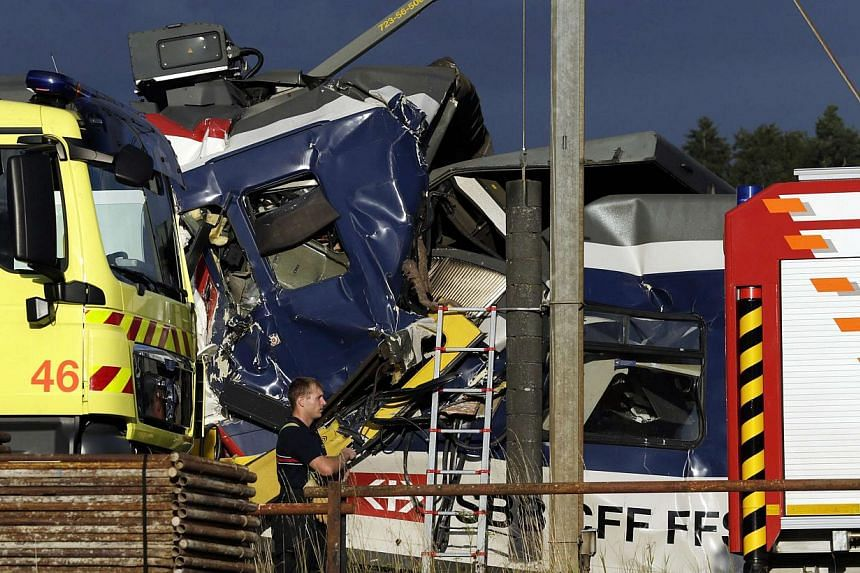 A rescue worker stands near two Swiss regional trains after a head-on collision near Granges-Pres-Marnand near Payerne in western Switzerland on July 29, 2013. The two trains collided in the Swiss canton of Vaud on Monday evening, injuring about 40 p