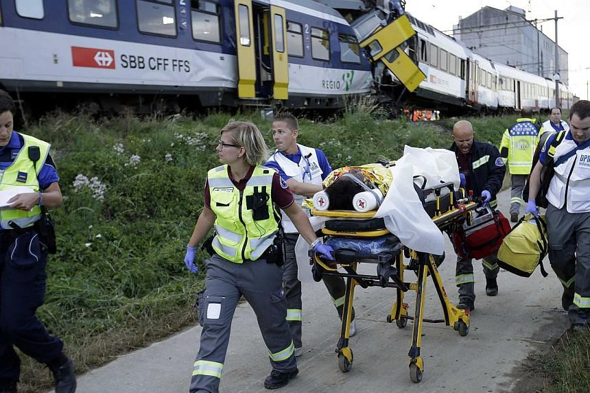 Swiss rescue workers wheel a wounded person on a stretcher after two regional trains crashed head on near Granges-Pres-Marnand near Payerne in western Switzerland on July 29, 2013. The two trains collided in the Swiss canton of Vaud on Monday evening