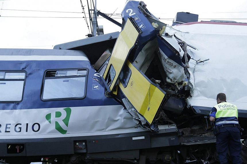 A police officer looks at the damage after a head on collision between two trains near Granges-pres-Marnand, near Payerne in western Switzerland, on July 29, 2013. The two trains collided at Granges-près-Marnand in the Swiss canton of Vaud on Monday