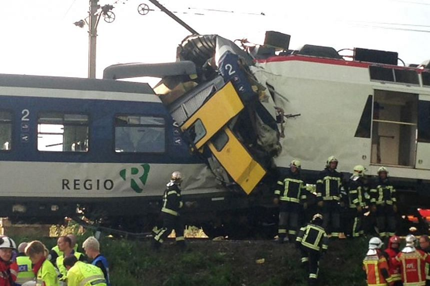 "This handout picture provided by ""24 heures/Tribune de Geneve"" shows the site of a collision of two trains on July 29, 2013 in Granges-pres-Marnand, Western Switzerland. Two trains collided head-on, injuring 40 passengers, at least five of them serio"